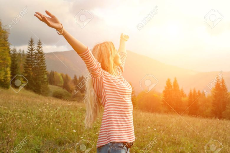 34106736-Happiness-woman-stay-outdoor-under-sunlight-of-sunset-Stock-Photo